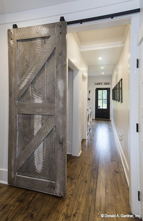 A rustic barn door opens to the utility room with white appliances and black-framed artworks fixed against the white walls.