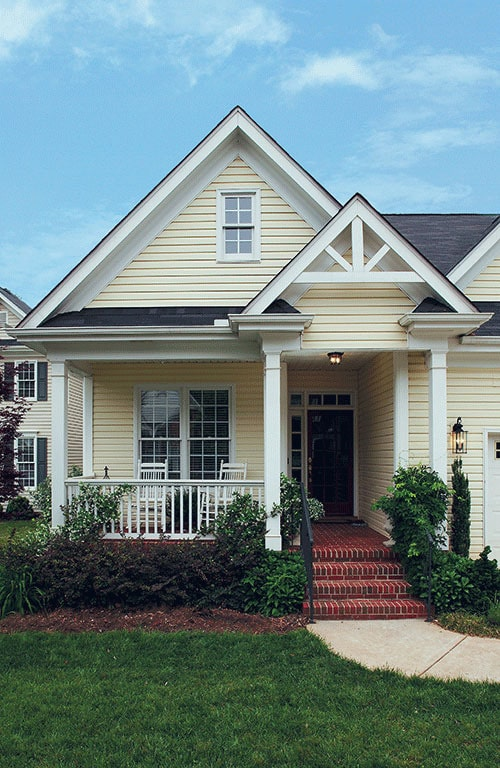 Home entry with a covered porch and a red brick stoop that matches the flooring.