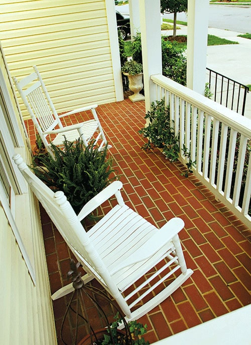 A pair of white rocking chairs along with fresh potted plants fill the covered front porch.