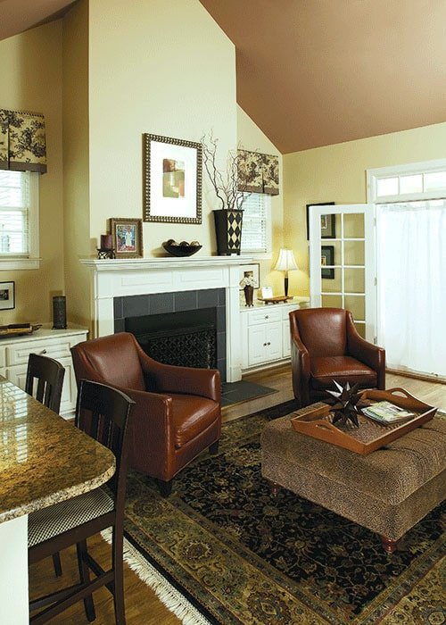 The living room offers a warm fireplace, brown leather armchairs, and a tufted ottoman over a tasseled area rug.