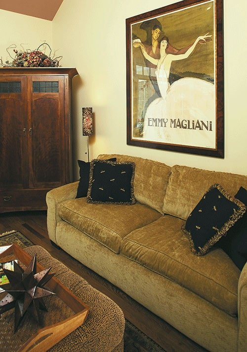 There's also a wooden cabinet and a velvet sofa placed under the large painting.