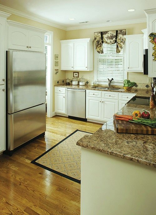 The kitchen is equipped with white cabinetry, granite countertops, and stainless steel appliances.