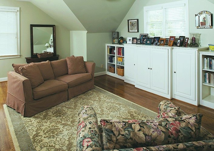 Bonus room furnished with floral and skirted seats, dark wood console table, and white cabinets topped with framed photos.