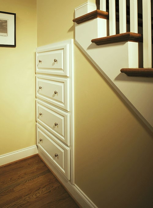 The traditional staircase is fitted with white drawers for additional storage.