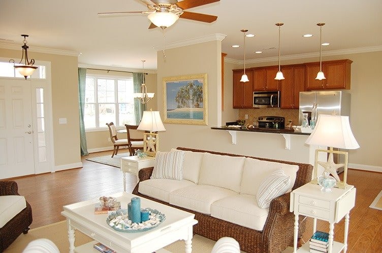 Sitting behind the living area is the kitchen with wooden cabinetry, stainless steel appliances, and ambient lighting.