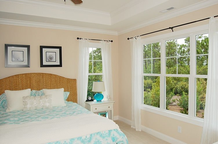 The primary bedroom has a cozy wicker bed and white framed windows dressed in sheer curtains.