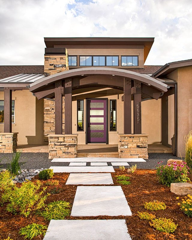 A concrete walkway leads to the covered front porch enclosed in a barrel roof and tapered columns.