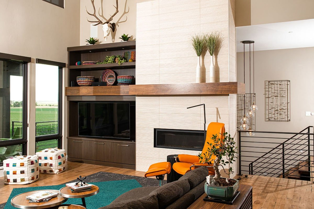 Living room with multi-colored seats, a modular coffee table, and a flatscreen TV situated next to the modern fireplace.