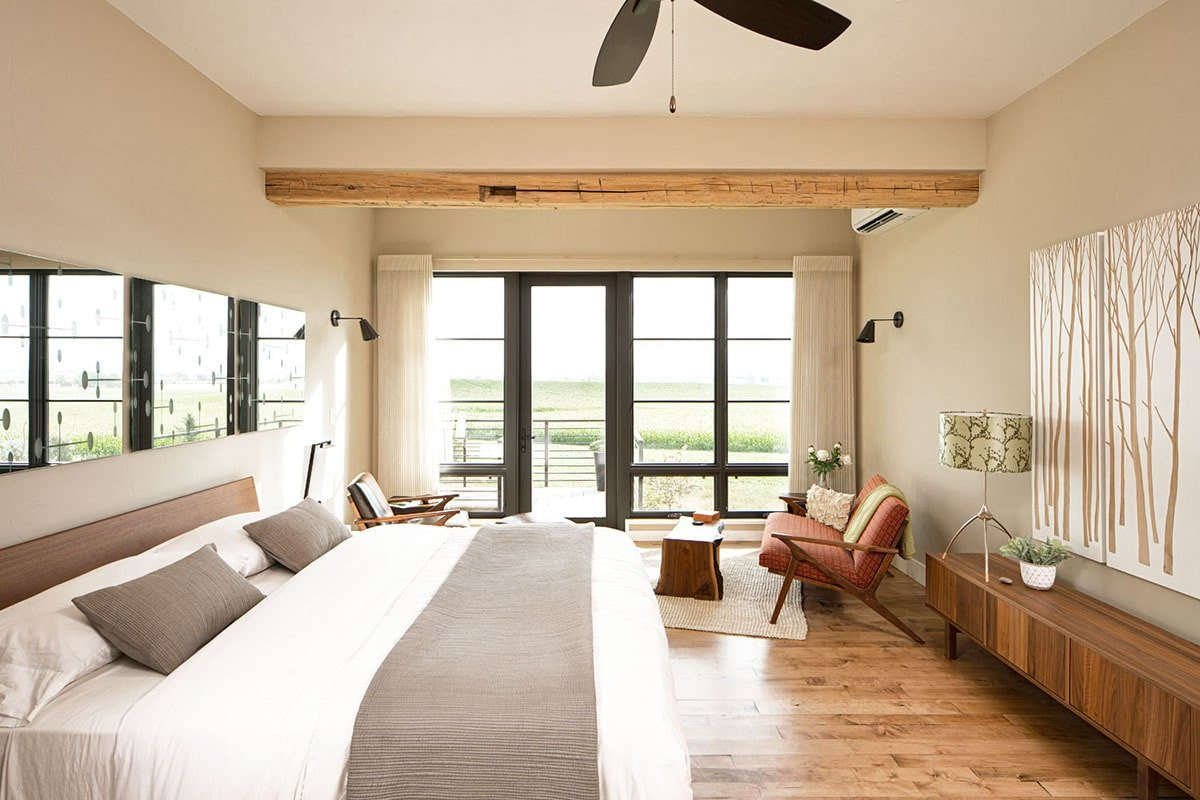 Primary bedroom with hardwood flooring, massive windows, and a regular ceiling lined with a rustic wood beam.