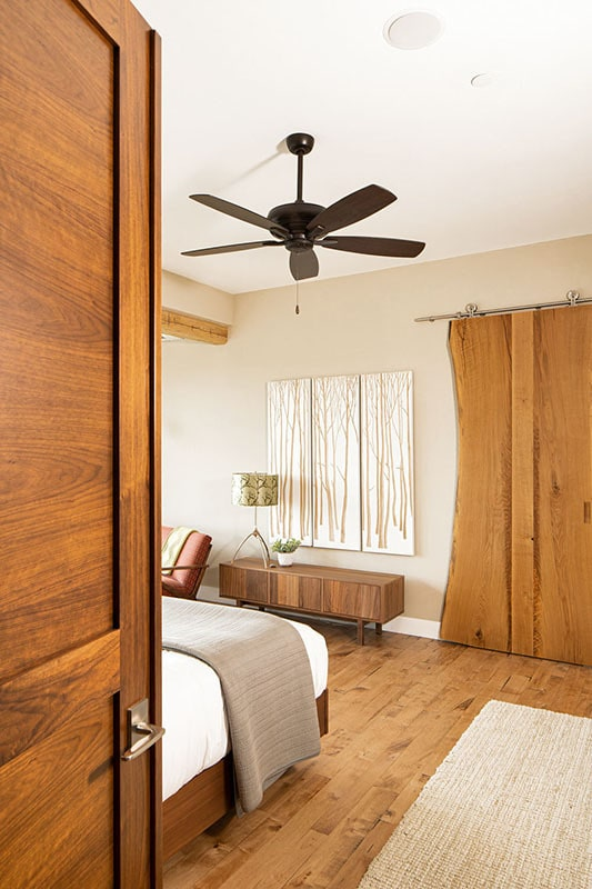 As you open the primary bedroom's door, you'll see a stylish barn door in front that leads to the primary bathroom.