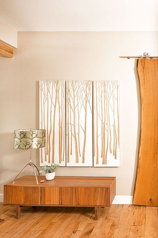 Three-panel artwork and a drum lampshade adorn the wooden console table.