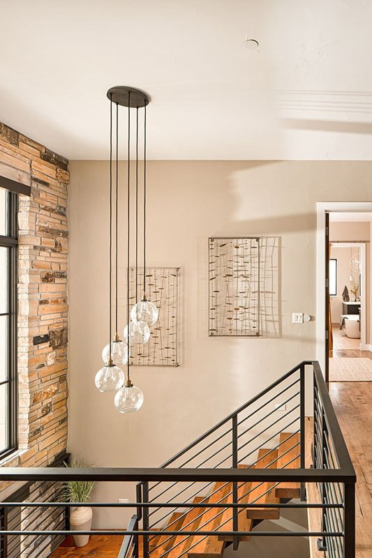 Cascading glass globe chandelier illuminates the staircase landing.
