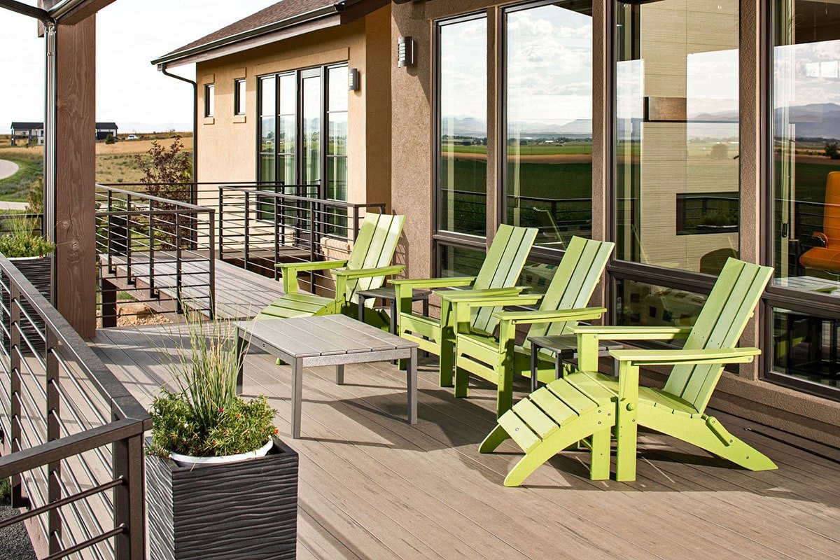 An expansive deck filled with green loungers, a wood plank table, and a potted plant.