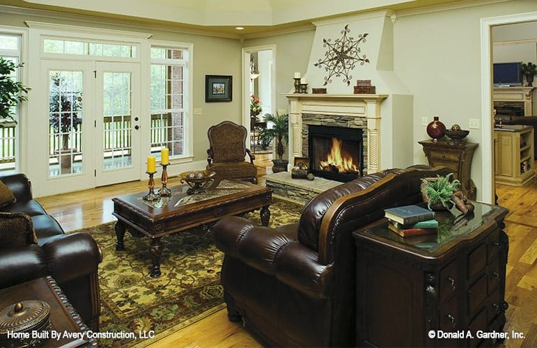 The living room offers a stone fireplace and brown leather seats paired with a wooden coffee table over a patterned area rug.