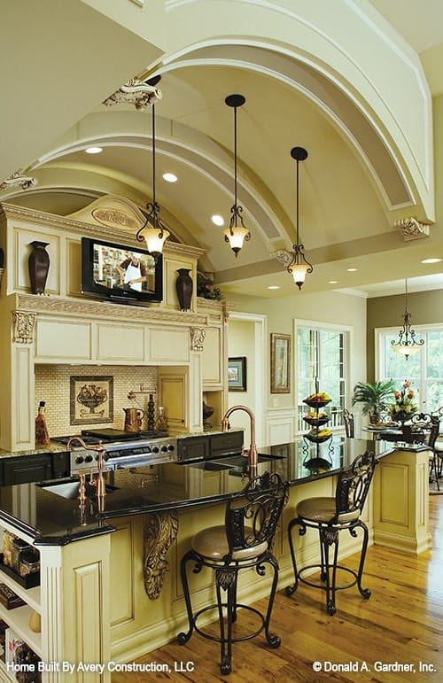 A barrel-vaulted ceiling mounted with wrought iron pendants and recessed lights crown the kitchen.