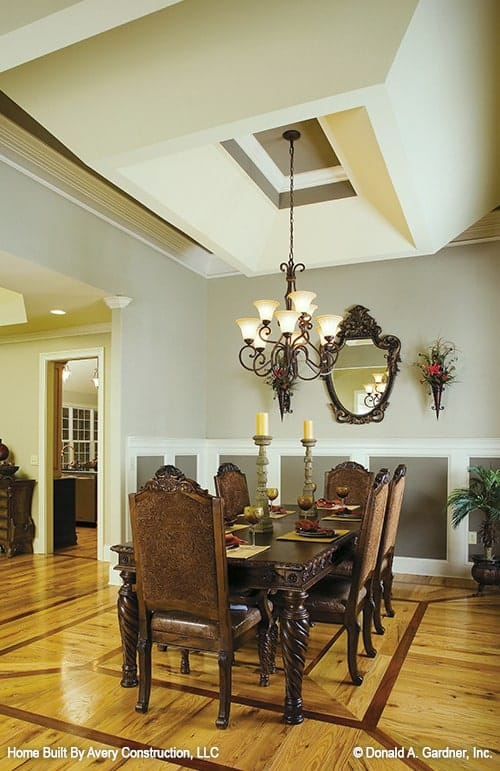 The formal dining room offers classy high back chairs and a rectangular dining table illuminated by an ornate chandelier.