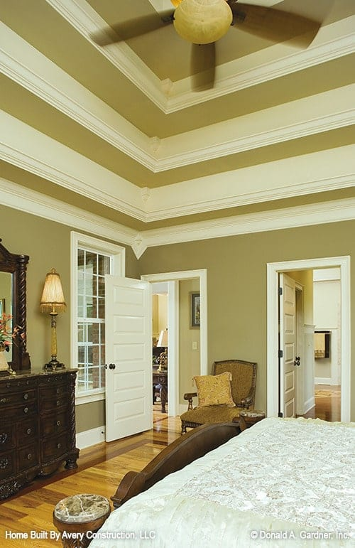 The primary bedroom has polished hardwood flooring and a stunning step ceiling that matches the moss green walls.