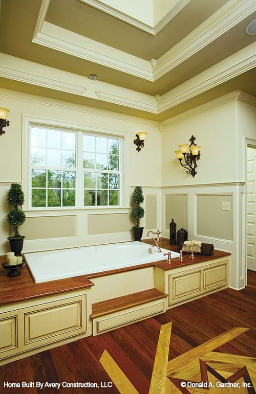 Primary bathroom featuring a deep soaking tub fixed against the beige wainscoting.