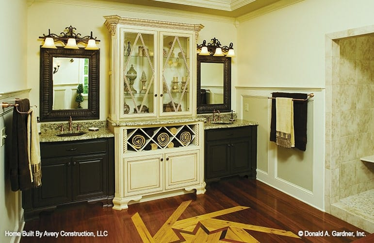 Dark wood vanities flank the cream glass front cabinet displaying antique decors and candle holders.