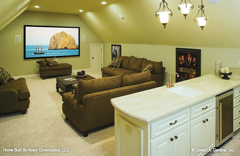 Media room with a white bar and comfy brown seats surrounding the wooden coffee table over the beige carpet flooring.
