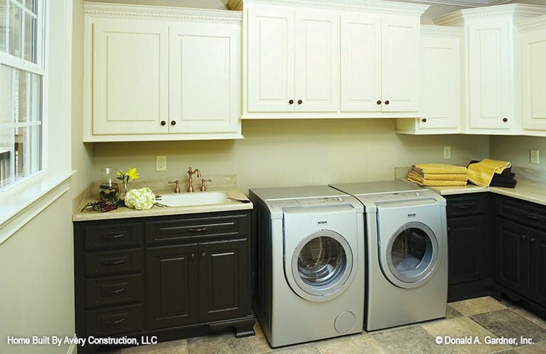 The utility room is equipped with front-load appliances, white upper cabinets, and black lower cabinets topped with an undermount sink.