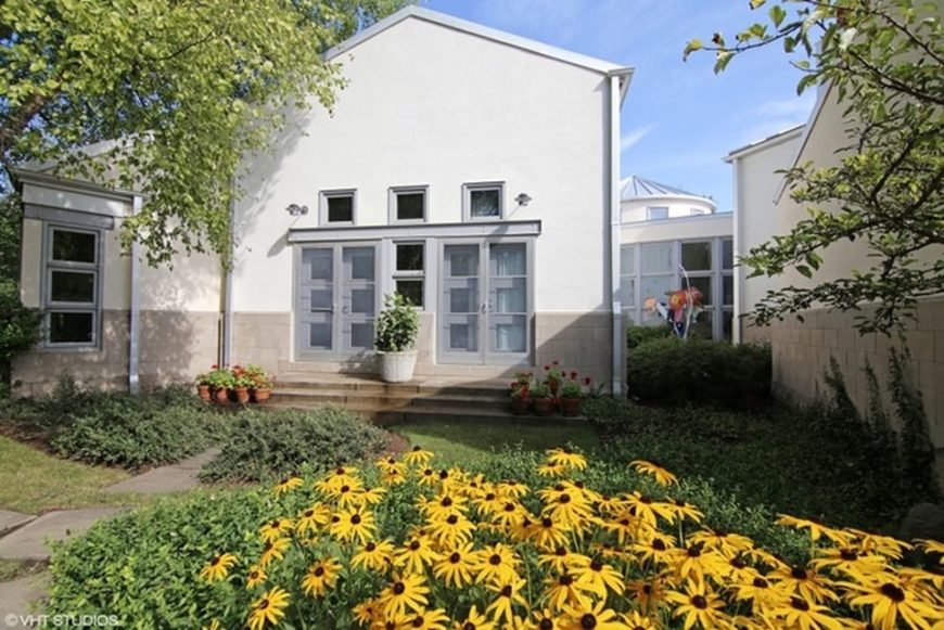 This is a view of the house from the backyard garden. Here you see the colorful flowering shrubs and landscaping that give color to the light beige exterior walls of the house. Image courtesy of Toptenrealestatedeals.com.