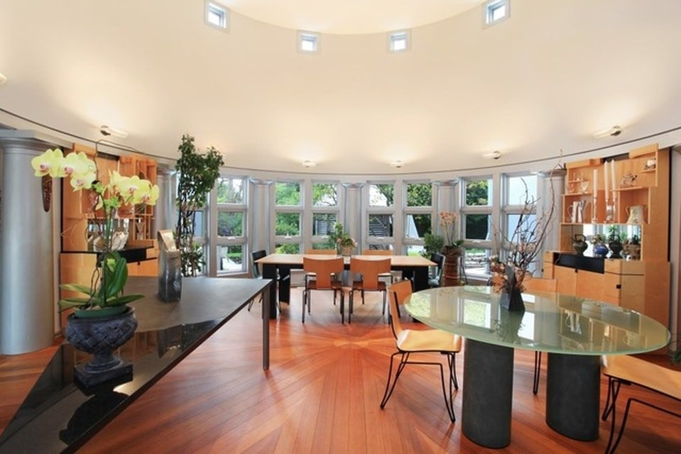 This is the spacious dining room with a tall beige cove ceiling and glass walls that bring in natural lighting for the two dining areas. Image courtesy of Toptenrealestatedeals.com.