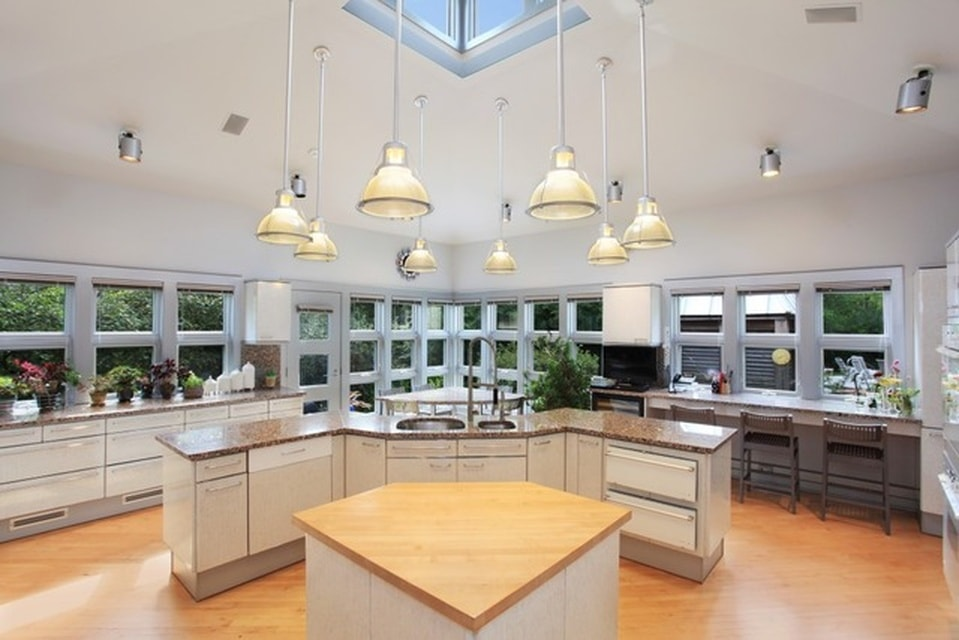 This kitchen has enough space for two kitchen islands. The smaller one has a wooden countertop that matches the hardwood flooring. These are then topped with pendant lights from the white ceiling. Image courtesy of Toptenrealestatedeals.com.