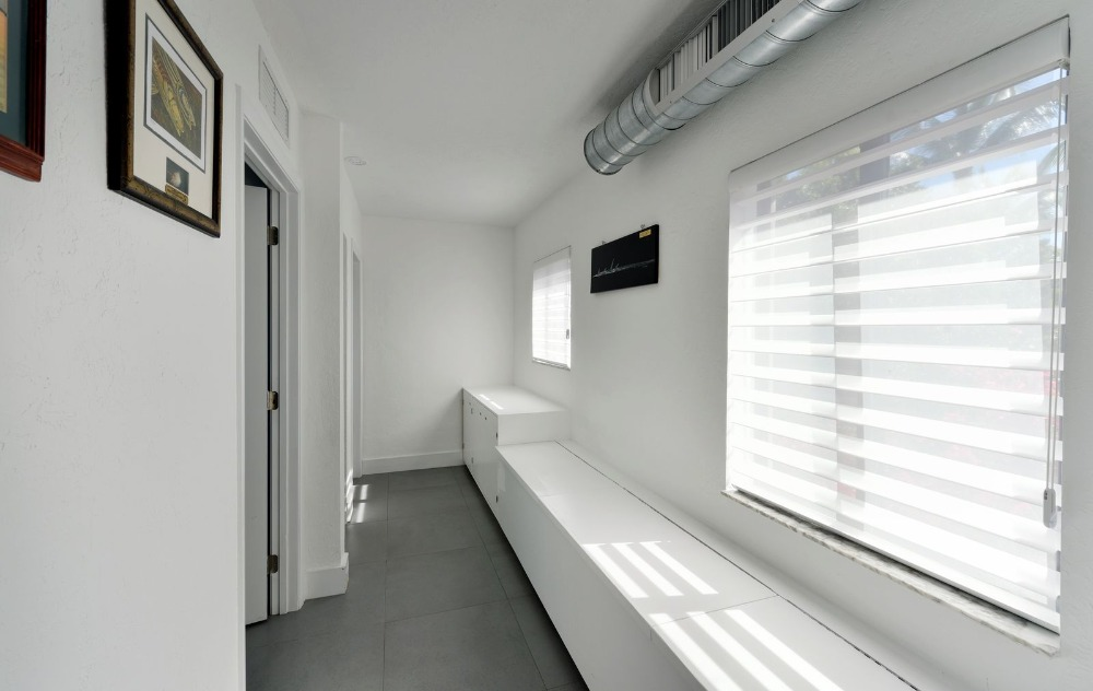 A room with a counter and a bench seat, along with glass windows protected by window blinds. Image courtesy of Toptenrealestatedeals.com.