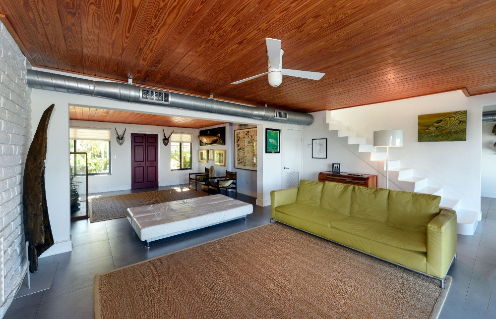 Living space featuring a green couch and a brown area rug. Image courtesy of Toptenrealestatedeals.com.