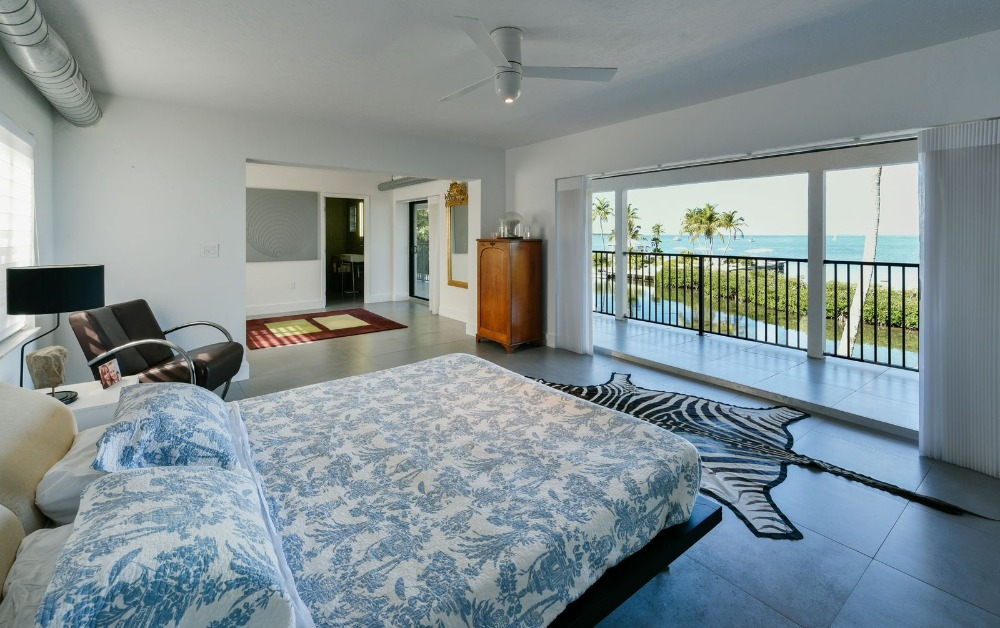 Bedroom suite with a modern bed set and a modern armchair on the side. Image courtesy of Toptenrealestatedeals.com.