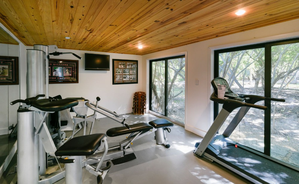There's a home gym too offering many equipment and features a wooden ceiling and glass windows. Image courtesy of Toptenrealestatedeals.com.