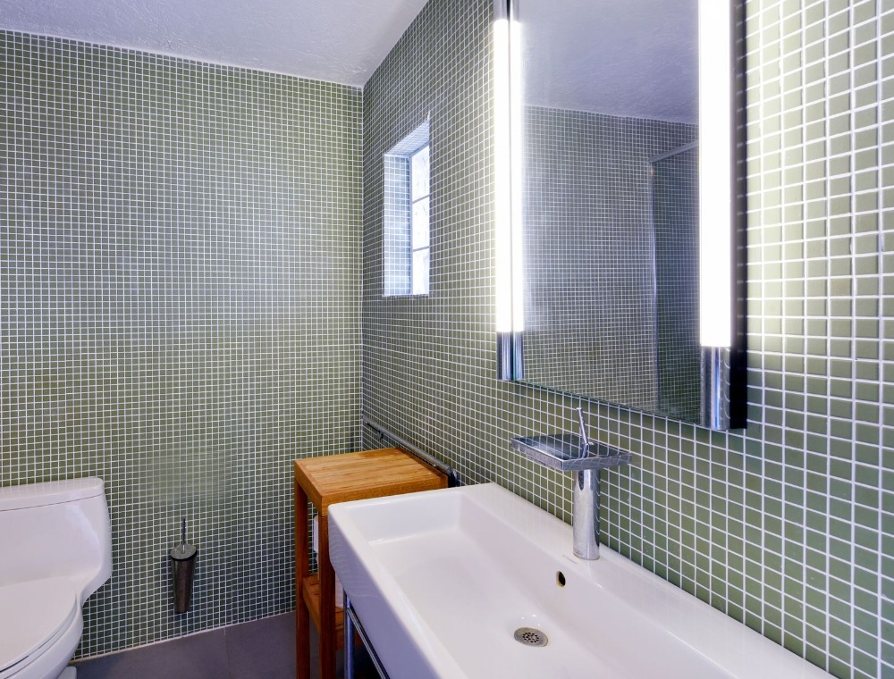 Bathroom with stylish tiles walls and a white sink counter. Image courtesy of Toptenrealestatedeals.com.