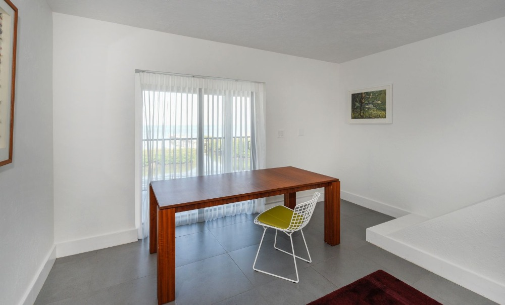 Simple room with a table and a chair, surrounded by plain white walls and ceiling. Image courtesy of Toptenrealestatedeals.com.