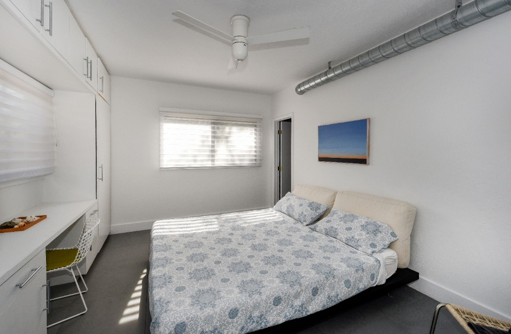 This bedroom offers a nice bed set, a study desk and a reach-in closet. Image courtesy of Toptenrealestatedeals.com.