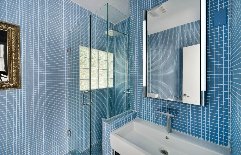 This bathroom features blue tiles walls, a walk-in shower and a sink counter. Image courtesy of Toptenrealestatedeals.com.