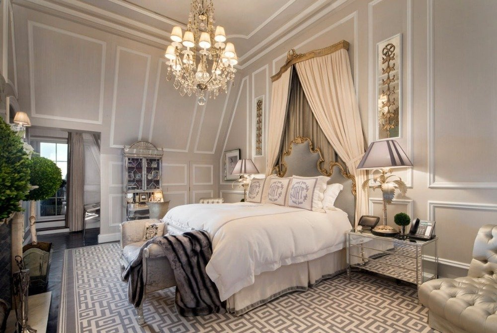 Primary bedroom suite with elegant walls and a custom high ceiling. The room offers a luxurious bed set with table lamps on both sides. Image courtesy of Toptenrealestatedeals.com.