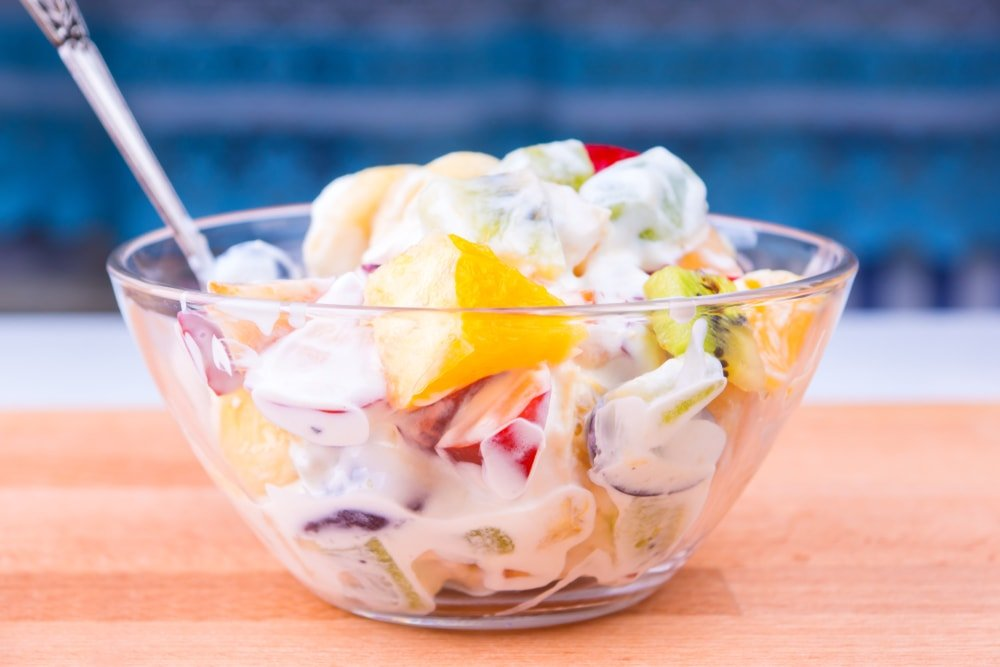A bowl of creamy tropical fruit salad.