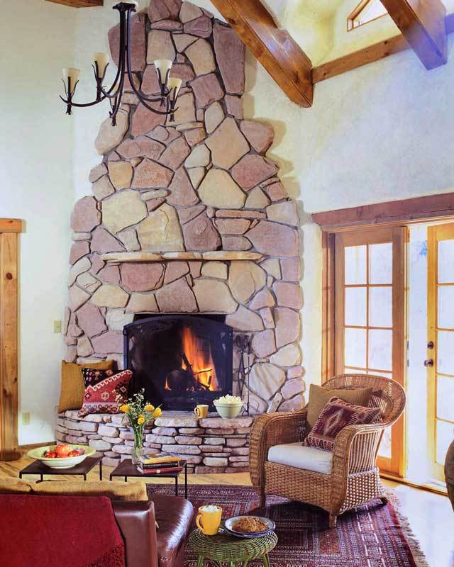 The living room offers wicker and leather chairs, metal coffee tables, and a kiva fireplace clad in striking stones.