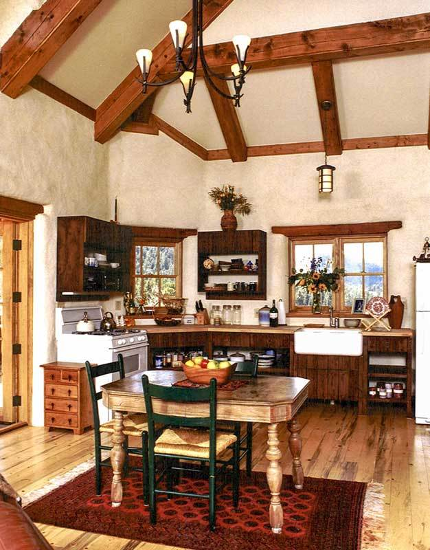 The eat-in kitchen is equipped with wooden and floating cabinets, a farmhouse sink, a white cooking range, and wooden dining set over a red patterned rug.