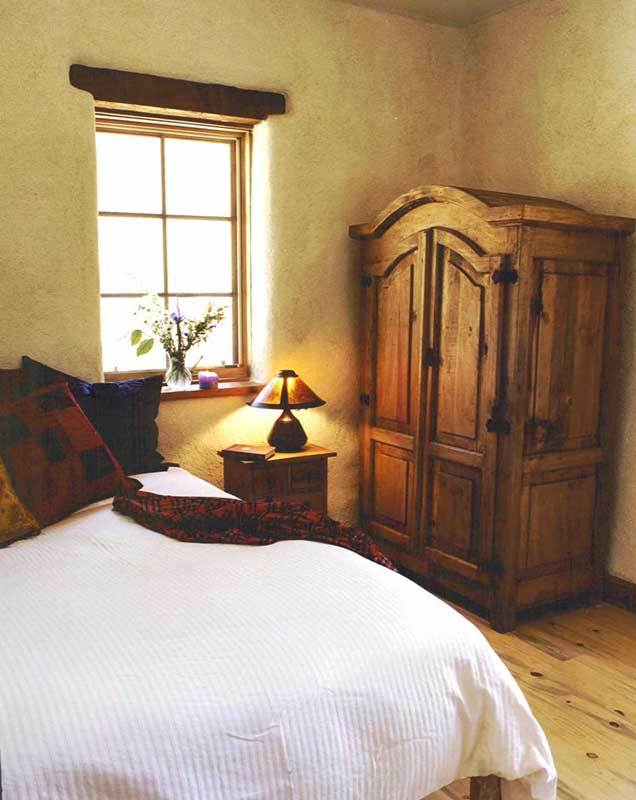 This bedroom offers a carved wood wardrobe and a cozy bed complemented with a wooden nightstand.