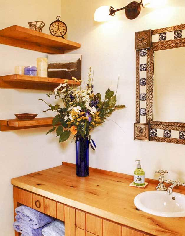 A powder room showcasing floating shelves and a wooden vanity paired with a stylish framed mirror.