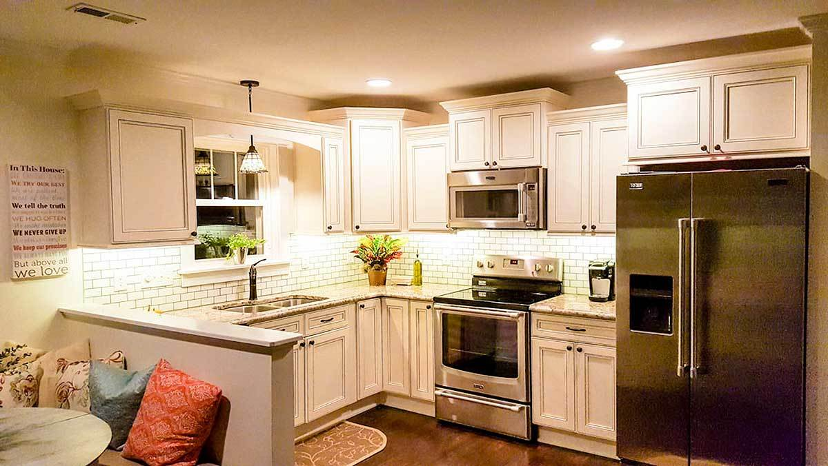 The kitchen is equipped with a double bowl sink, stainless steel appliances, white cabinets, and a peninsula that acts as a divider to the dining area.