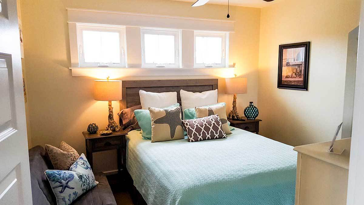The primary bedroom has white framed windows, a cozy gray sit, and an upholstered bed flanked by wooden nightstands and drum table lamps.