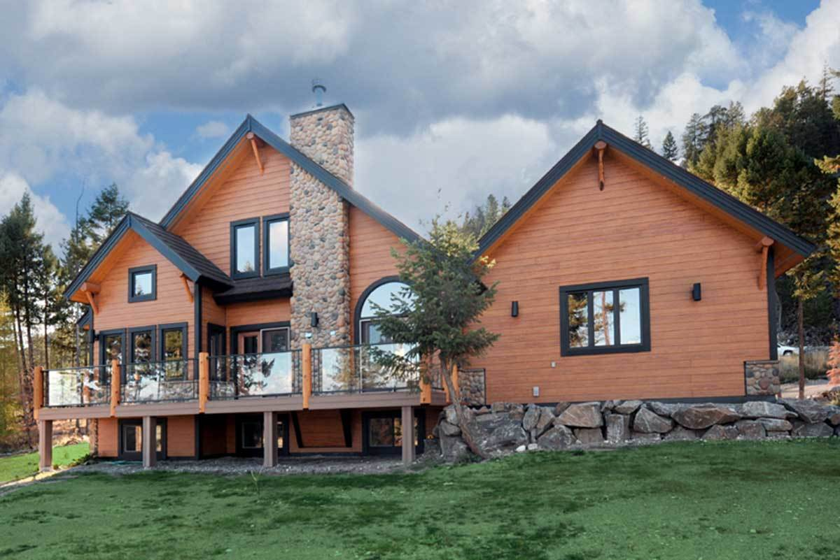 This is a close look at the mountain-style home with earthy brown wooden shiplap exterior walls accented with black details, roofs and frames of doors and windows. These are then complemented by the glass windows, railings and the large stone mosaic chimney.