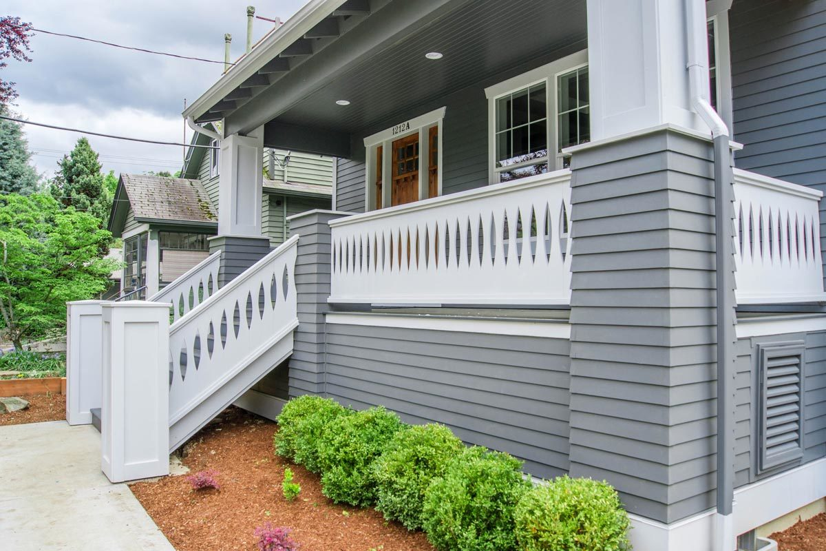 A gray stoop framed with decorative railings and wainscoted posts leads to the home's front porch.