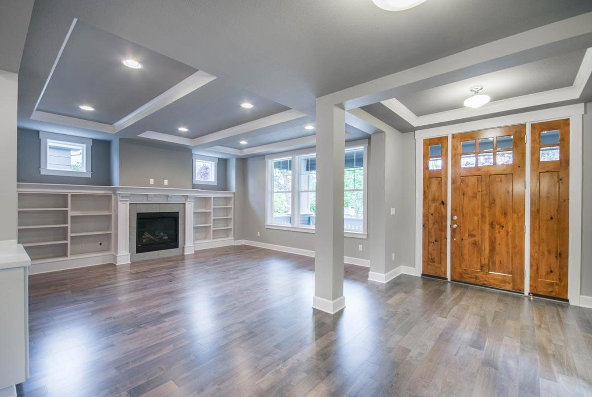 The foyer has a tray ceiling and a natural hardwood flooring that extends to the living room.