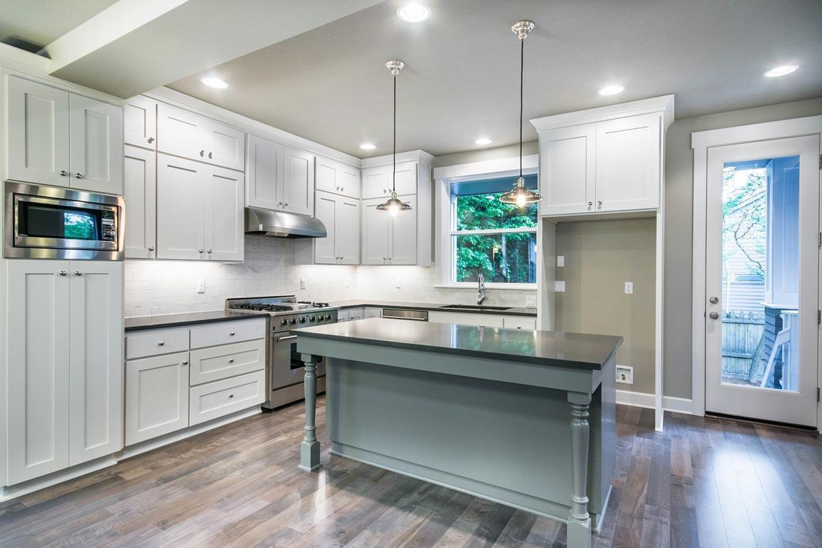 Kitchen with white custom cabinets, black granite countertops, and a center island lit by done pendant lights.