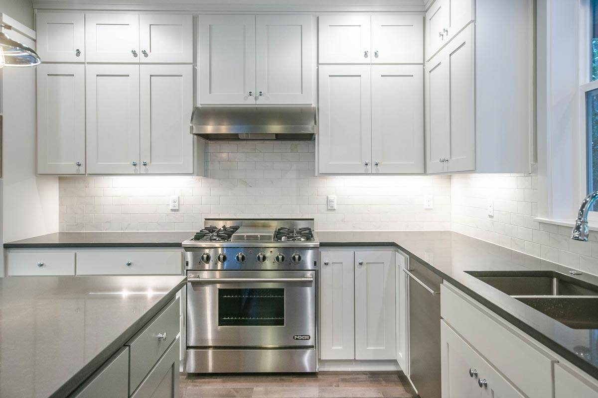 The stainless steel range with a matching vent hood on top sits in between the white cabinets.