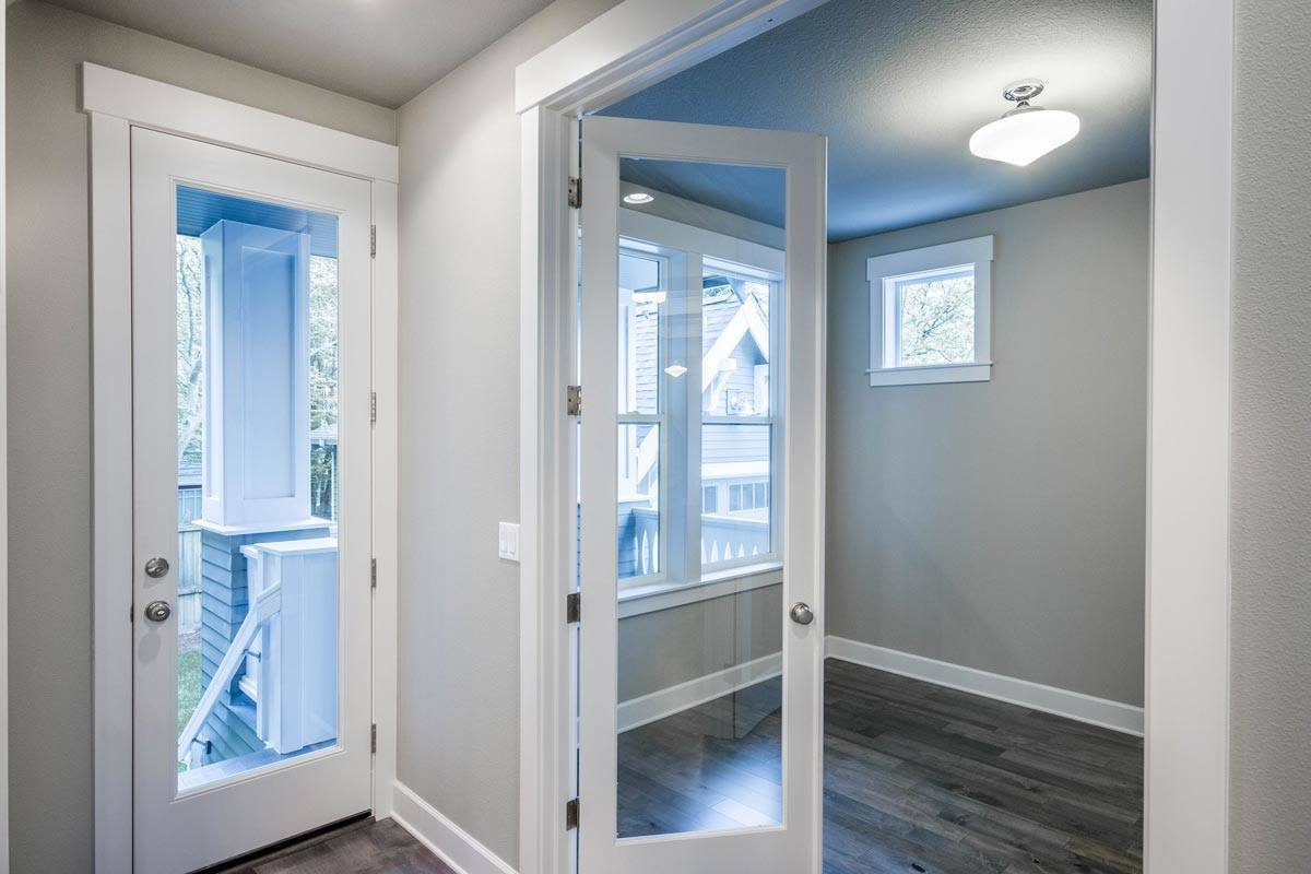 White framed windows and a semi-flush mount light brightens the den that's enclosed in a double glass door.
